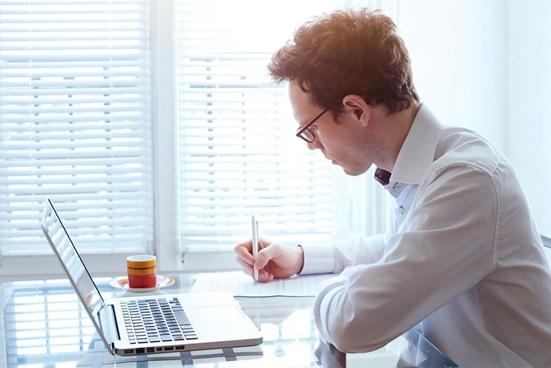Photo of young business man working in office