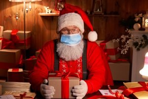 Photo of Santa Claus wearing face mask, holding gift box preparing for xmas eve sitting at cozy home table late in night with presents.