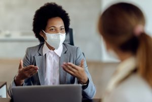 Black female consultant talking to her client and wearing protective face mask during the meeting.