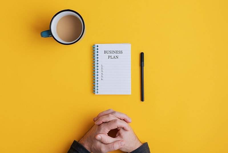 Man sitting by spiral notebook with Business plan ideas ready to be written in it. Over yellow background with copy space.