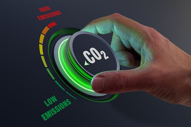 Concept image of person turning a dial to reduce level of CO2