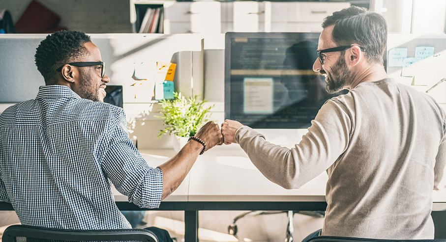 Photo of two colleagues fist bumping at their desks