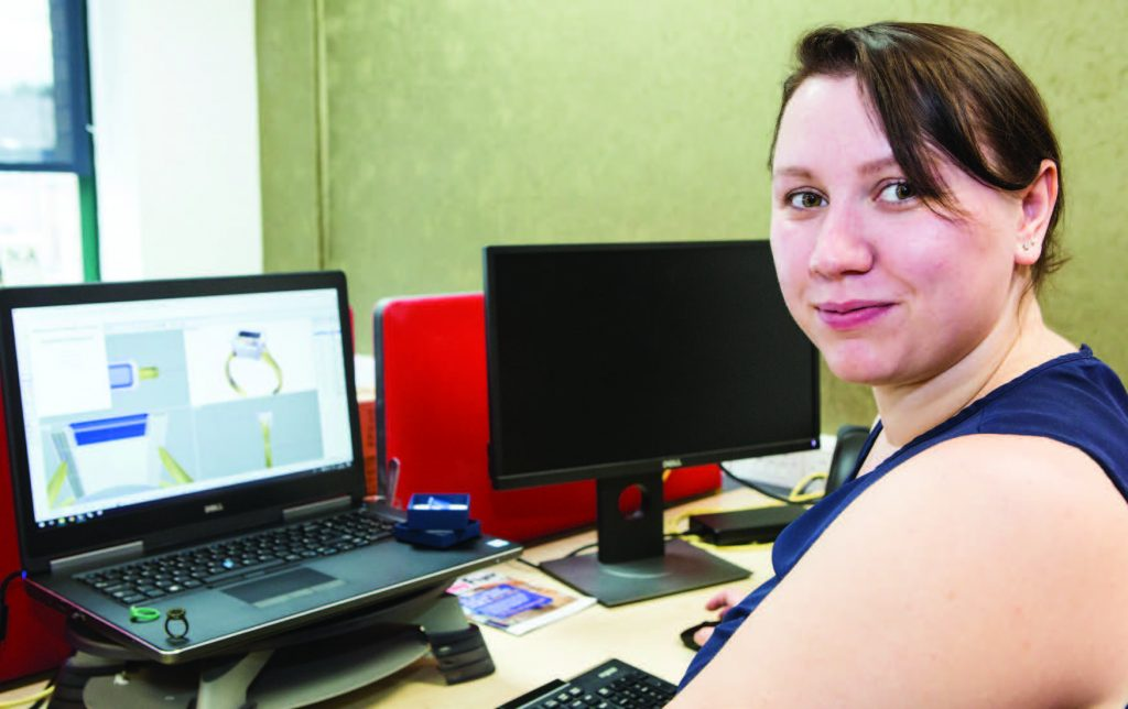 Photo of KTP Associate Jade Pelham sat in front of a computer that has 3D modelling software loaded on the screen