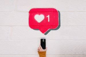 Photo of person holding a mobile phone, with a graphic of the twitter like heart above.